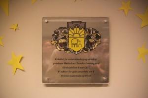 Plaketten linjeforeningen fikk i gave av Fakultet for naturvitenskap og teknologi