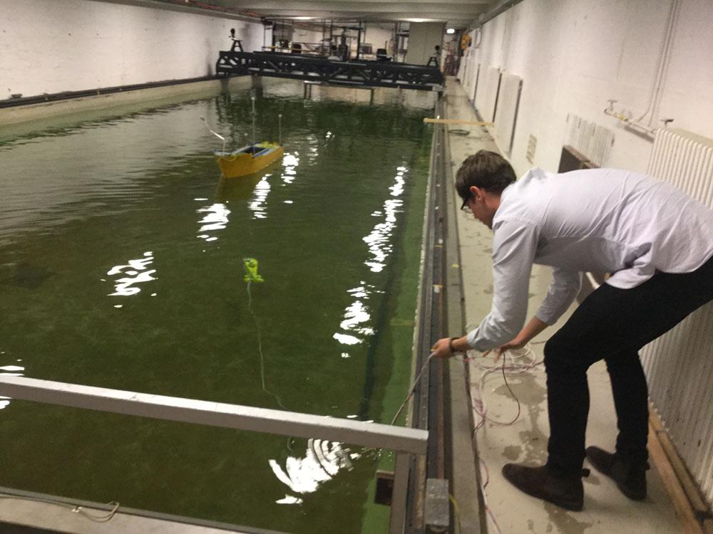 Masterstudent Erik Valle slipper mini-undervannsfartøyet Neptunus ut i et av testbassengene ved Marinteknisk senter. I bakgrunnen sees et av modellskipene som brukes til å forske på dynamisk posisjonering. Valle og hans medstudenter undersøker blant annet muligheten for å utstyre Neptunus med dynamisk posisjonering.